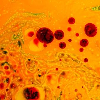 Abstrait jaune irréel avec des gouttelettes rouges