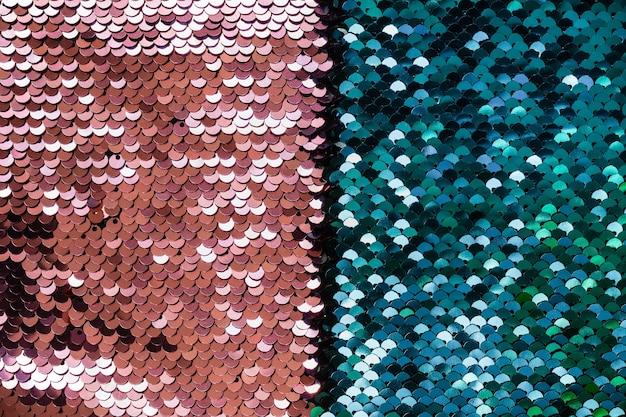Abstrait de luxe avec des paillettes de corail et turquoise sur tissu.