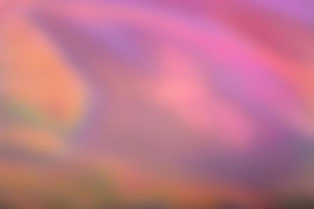 Abstrait magenta rose floue fond de feuille irisée holographique. dégradé tendance avec des couleurs vives