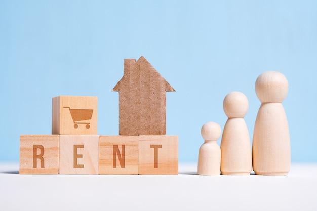 Abstrait maison en carton à côté d'une famille arbitraire: maman, papa, bébé mot acheter sur des cubes à louer. location de logement.