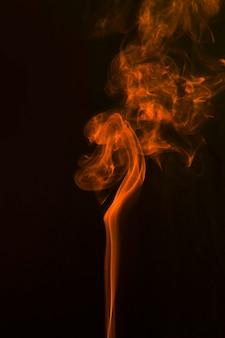 Abstrait noir avec une fumée orange vaporeuse