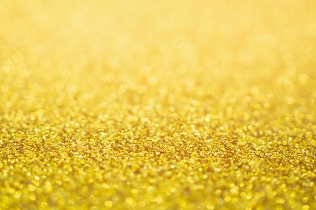 Abstrait paillettes d'or festif fond de texture de noël flou avec lumière bokeh