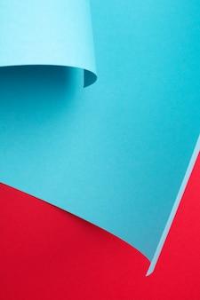 Abstrait de papier courbe. cadre d'art, espace de copie. couleurs géométriques rouges et bleues. mise à plat minimale.