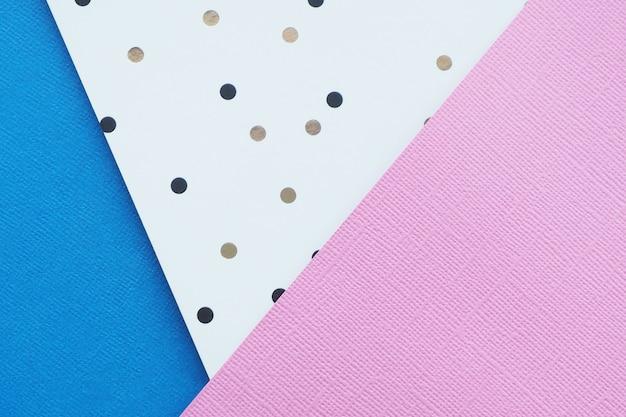 Abstrait de papier rose, bleu et blanc à pois noirs et bruns.