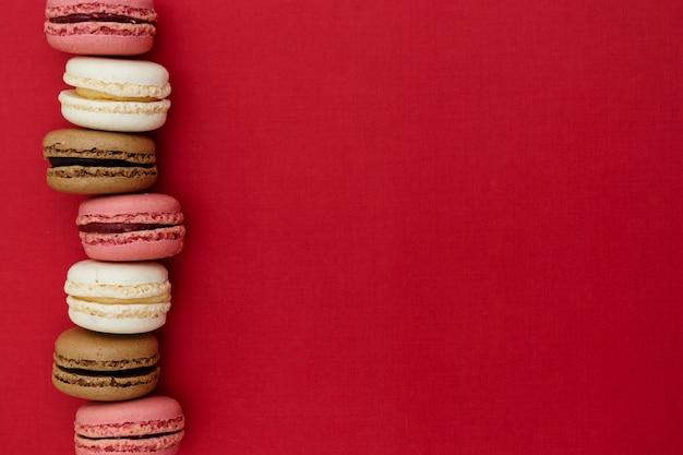 Abstrait photo alimentaire avec des macarons sur fond rouge.