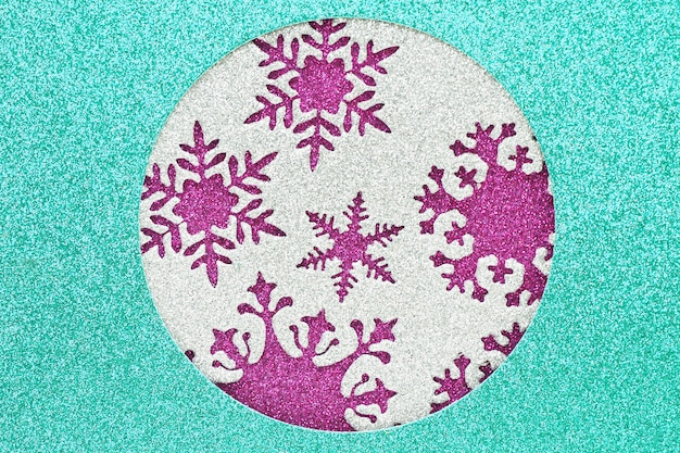 Abstrait et texture d'un matériau brillant bleu avec un trou rond, à l'intérieur du trou, il y a un matériau argenté avec des flocons de neige découpés sur un fond brillant violet.