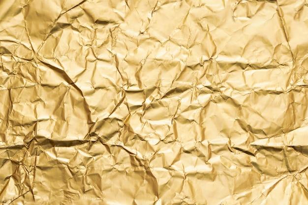 Abstrait de texture de papier d'aluminium froissé doré