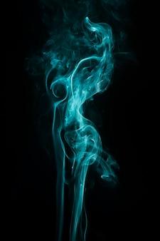 Abstrait tourbillonnant de fumée turquoise sur le fond noir