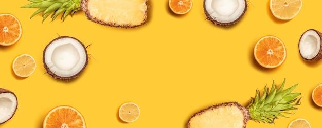 Abstrait tropical. ananas, citrons, oranges et noix de coco sur fond jaune.