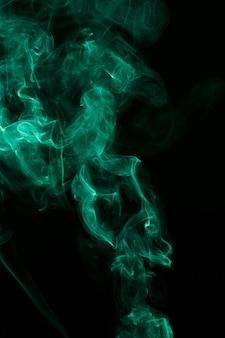 Abstrait vert fumée vaporeuse se propage sur fond noir
