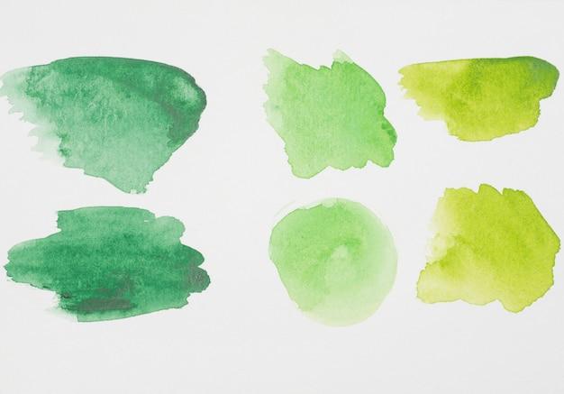 Abstraits points verts de peintures sur papier blanc