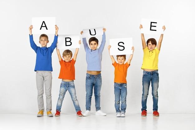 L'abus nous rend malade. groupe d'enfants tristes et en colère avec des bannières blanches tenant un mot isolé sur fond de studio. concept d'éducation et de publicité. concepts de protestation et de droits de l'enfant.