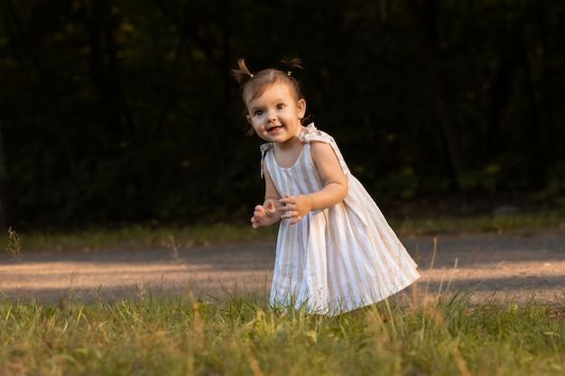 Aby girl s'amuse dans le parc, courir pieds nus sur l'herbe verte.