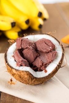Açai brésilien sur une coque de noix de coco avec un fond de bois et de fruits.