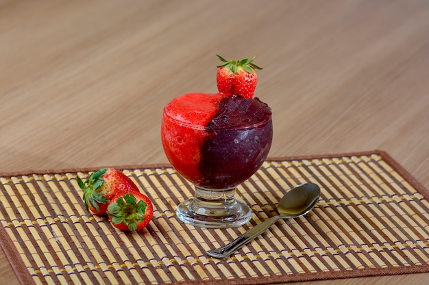Açai congelé et bol de crème aux fraises fraîches sur une table en bois rustique, délicieux dessert