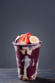 Açaí congelé brésilien dans une tasse en plastique avec du lait concentré, de la banane et de la fraise. fruit de l'amazonie.