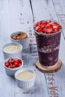 Açaï congelé dans un gobelet en plastique avec fruits et accompagnements, granola, lait en poudre, fraise et lait concentré. espace de copie