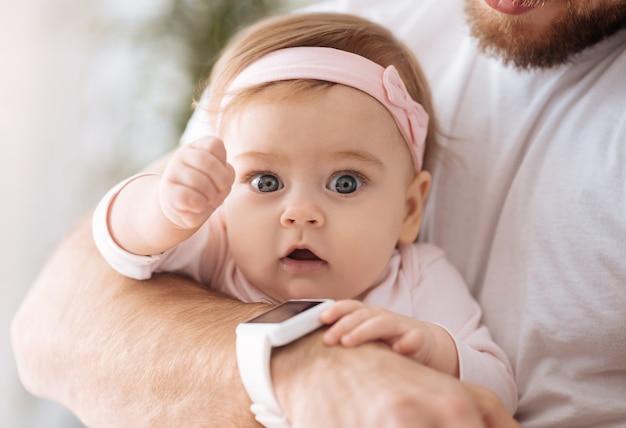 Accablé d'émotions. doux agréable bébé fille impliquée se trouvant entre les mains du père et regardant ailleurs tout en exprimant son intérêt et sa joie
