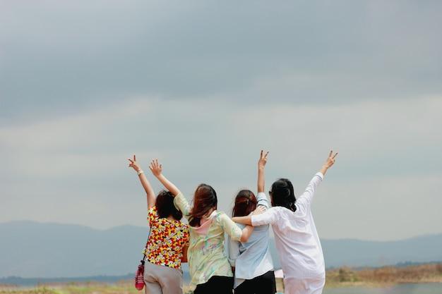 Accent doux et flou avec des amis de la femme heureuse s'amusant et exprimant leurs émotions regardant la montagne