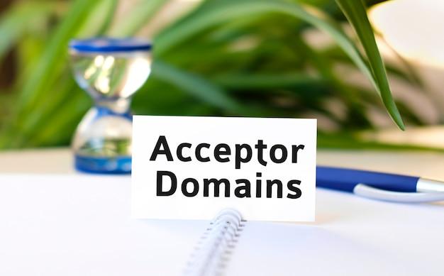 Acceptor domain seo business concept texte sur un cahier blanc et un sablier, stylo bleu, fleurs vertes