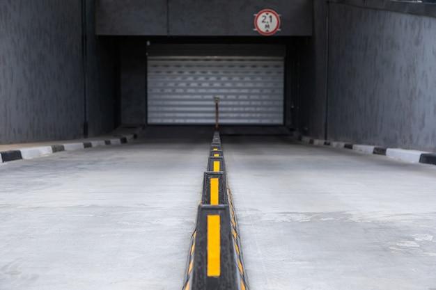 Accès au parking souterrain avec porte à volet roulant et séparateurs routiers avec bâtons jaunes