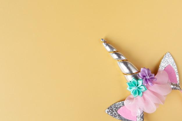 Accessoire de fête d'halloween, jante avec oreilles et corne de licorne. fond jaune pastel, espace copie. appartement de vacances poser. style minimal. horizontal