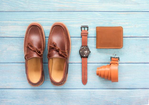 Accessoire homme avec chaussure mocassins, porte-monnaie en cuir, montre marron et ceinture isolée sur un fond en bois bleu. vue de dessus.