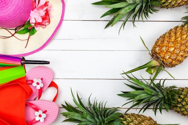 Accessoire de plage, chapeau, lunettes de soleil, chaussures et ananas sur bois blanc, voyage d'été et vente d'été