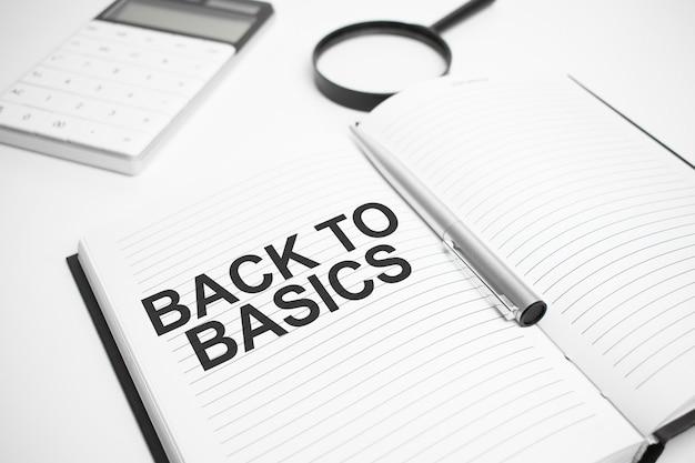 Accessoires d'affaires, calculatrice, rapports et loupe avec texte retour à l'essentiel