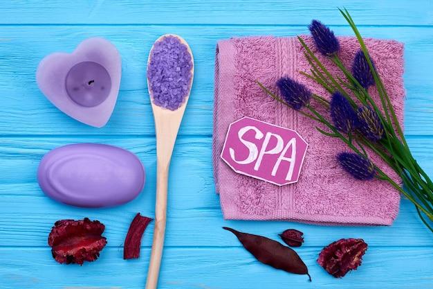 Accessoires aromatiques de salle de bain spa à plat sur bois bleu. savon au sel de mer, fleurs et pétales.