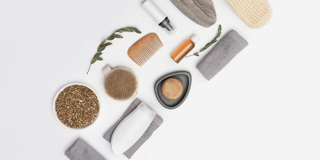 Accessoires de bain avec bouteilles avec gel ou shampoing, savon, sel marin, gant de toilette, peigne en bois