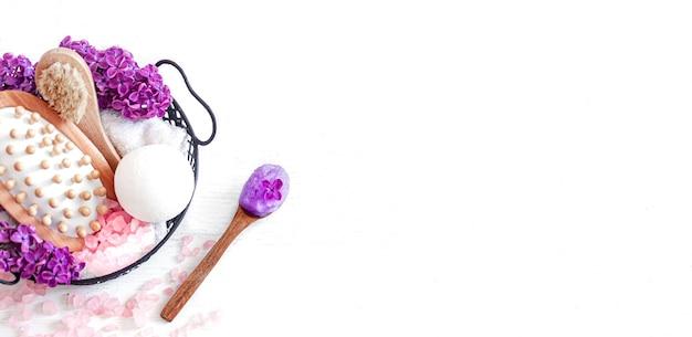 Accessoires de bain dans un panier avec une branche lilas se bouchent. espace de copie de concept de beauté et de soins du corps.