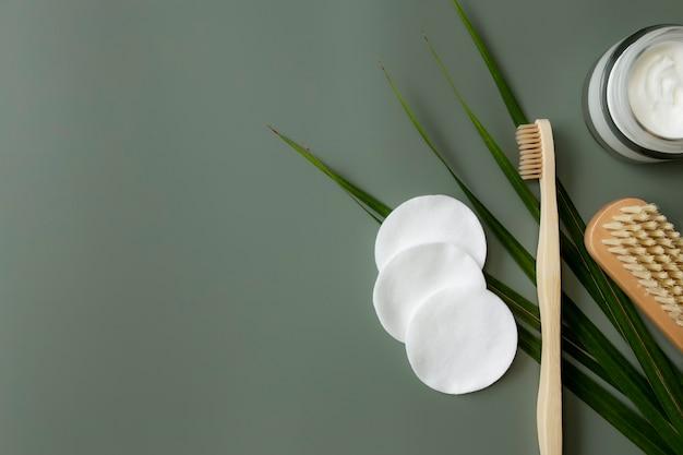Accessoires de bain flay lay, fond vert pastel. concept de soins de santé, feuille de palmier, brosse à dents en bois, brosse à pieds, tampons de coton, bouteille de crème. eco, zéro déchet, concept d'environnement réutilisable et sans plastique