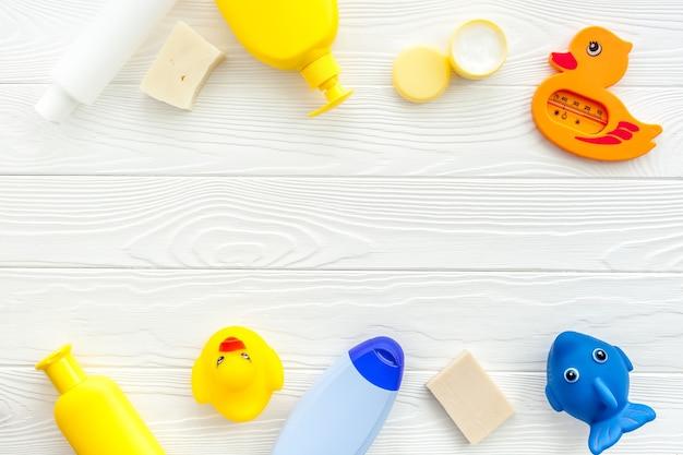 Accessoires de bain pour enfants sur fond de bois blanc