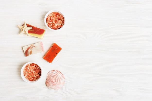 Accessoires de bain, savon bio bricolage et sel de mer de couleur rose sur une surface en bois blanche