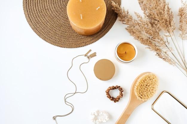 Accessoires de beauté / mode pour femmes et produits de soins de la peau sur fond blanc. bougie, bouquet d'herbe de pampa, cache-yeux, collier, pinceau. collage de style de vie minimal. mise à plat, vue de dessus.