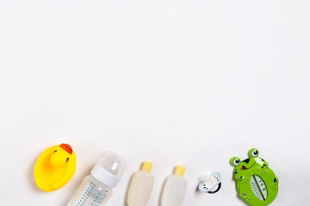 Accessoires bébé pour le bain avec canard sur fond blanc. vue de dessus. espace de copie. nature morte. mise à plat