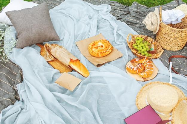 Accessoires chapeaux et panier pique-nique sur la pelouse sur une couverture avec baguette croissants raisins