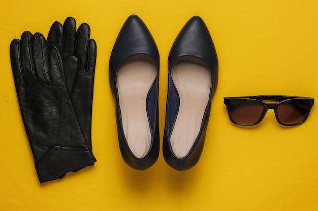 Accessoires et chaussures pour femmes élégantes sur fond jaune chaussures en cuir à talons hauts gants lunettes de soleil vue de dessus