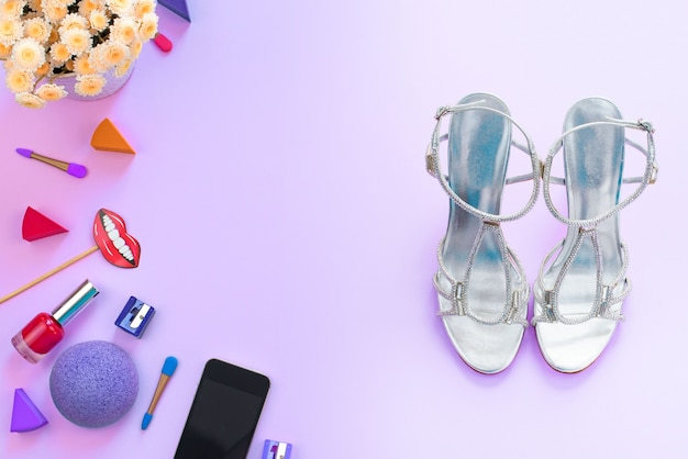 Accessoires cosmétiques chaussures gadget mobile fleurs fond violet