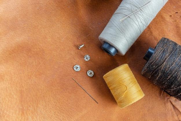 Accessoires de couture. ciseaux, aiguille, dé à coudre sur cuir