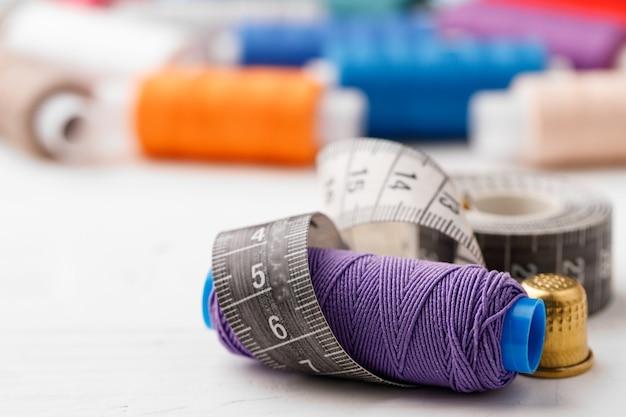 Accessoires de couture colorés sur table en bois blanc