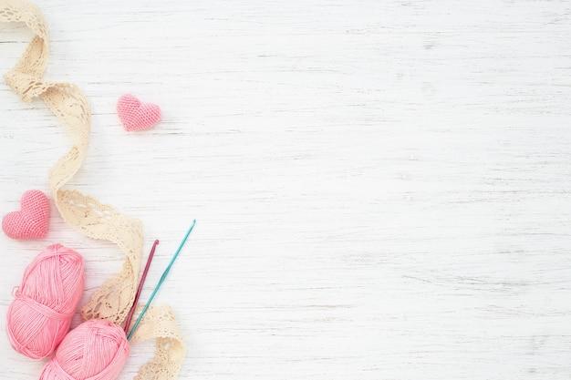Accessoires de couture, crochets, fil et coeurs sur tableau blanc