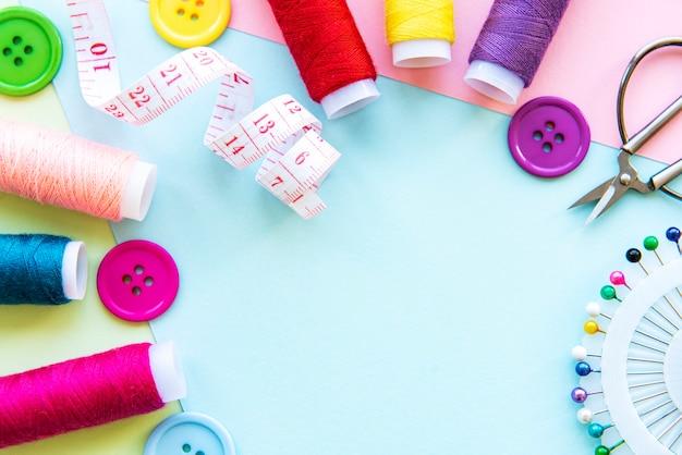 Accessoires de couture sur fond bleu pastel. fils à coudre, aiguilles, épingles, boutons et centimètre à coudre. vue de dessus, mise à plat.