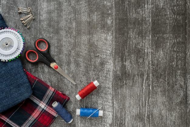 Accessoires de couture, jeans et tissu écossais sur un fond en bois foncé.