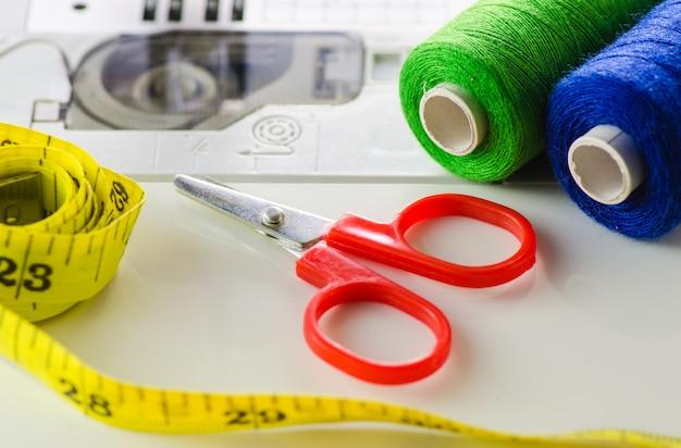 Accessoires de couture se trouvent sur un gros plan de machine à coudre blanche