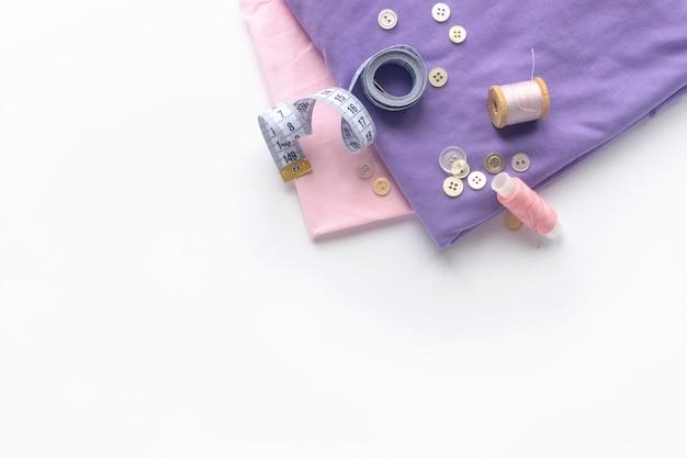 Accessoires de couture et tissu sur fond blanc