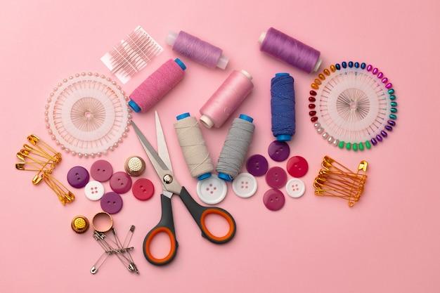 Accessoires de couture, y compris les bobines de fil et les épingles sur fond rose