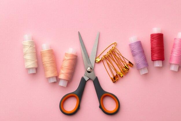Accessoires de couture, y compris des bobines de fil et des épingles sur une surface rose
