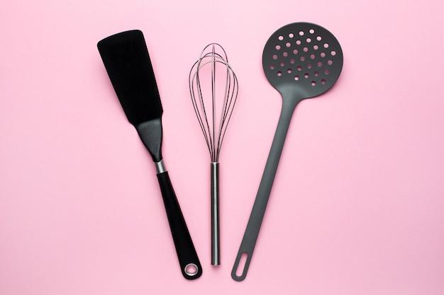 Accessoires de cuisine spatule fouet sur fond rose